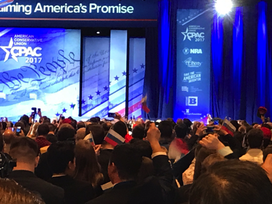 Photograph of CPAC attendees waving Russian flags before Donald Trump speaks